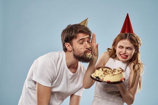 Ein mann und eine frau an einem geburtstag mit einem cupcake und einer kerze in einer festlichen mütze haben spaß und feiern gemeinsam die feiertage, glückliches paar
