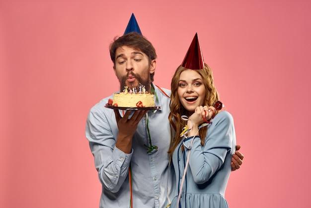 Ein mann und eine frau an einem geburtstag mit einem cupcake und einer kerze in einer festlichen mütze haben spaß und feiern gemeinsam die feiertage