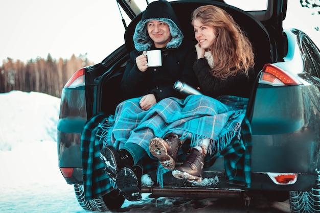 Ein mann und eine frau auf dem lastwagen des autos. ein glückliches paar, eingehüllt in eine warme strickdecke, trinkt heißen tee oder kaffee aus einer thermoskanne vor der kulisse des winterwaldes,
