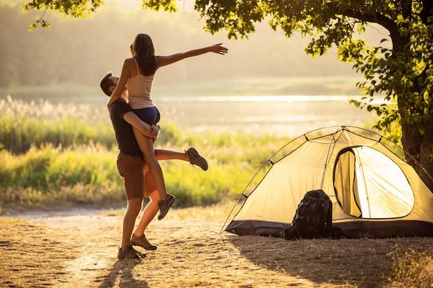 Ein mann und eine frau bei einer wanderung mit rucksäcken in der nähe eines zeltes bei sonnenuntergang umarmen sich.