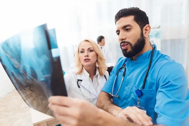 Ein mann und eine frau betrachten das röntgenbild des beckens.