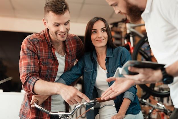 Ein mann und eine frau betrachten verschiedene fahrräder und details.