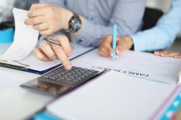 Ein mann und eine frau bilden das familienbudget auf basis von konten. nahaufnahme, männliche hände drücken den taschenrechner, weibliche hände machen sich notizen.
