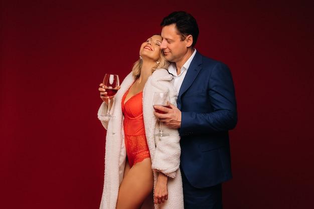 Ein mann und eine frau, die sich in ein glas champagner auf rotem hintergrund verliebt haben, umarmen sich.