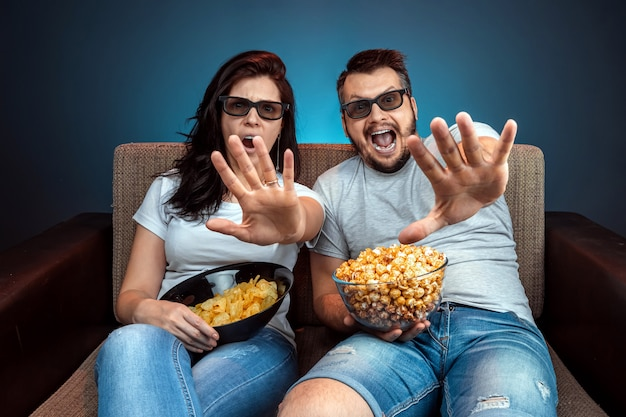Ein mann und eine frau, eine familie, die einen film oder eine serie in einer 3d-brille sieht, eine blaue wand. das konzept eines kinos, filme, emotionen, überraschung, freizeit, streaming-plattformen.