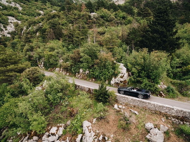 Ein mann und eine frau fahren in einem offenen auto einen malerischen weg in den bergen in montenegro entlang
