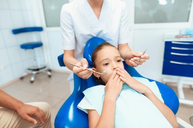 Ein mann und eine frau führten das mädchen zu einem zahnarzt