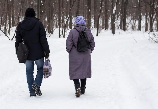 Ein mann und eine frau gehen durch einen winterpark und unterhalten sich süß miteinander.