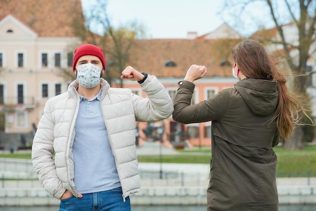 Ein mann und eine frau in gesichtsmasken stoßen an die ellbogen, anstatt sie mit einer umarmung zu begrüßen