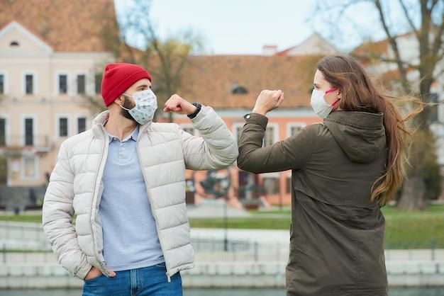 Ein mann und eine frau in masken stoßen an die ellbogen, anstatt mit einem handschlag zu grüßen.