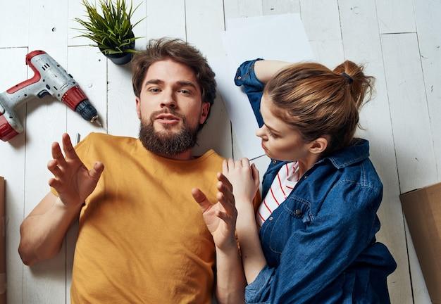 Ein mann und eine frau liegen auf dem boden eine kiste mit sachen zur renovierung der wohnungseinweihung draufsicht