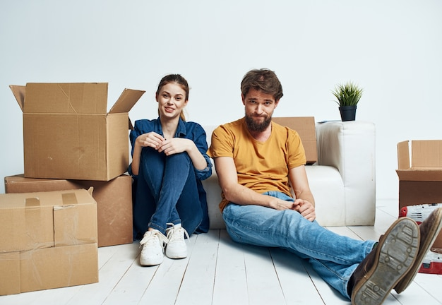 Ein mann und eine frau mit kisten ziehen um. nun, eine wohnung wird von einer familie renoviert.