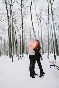 Ein mann und eine frau mit wunderkerzen auf dem hintergrund eines schneebedeckten waldes in einem schneefall