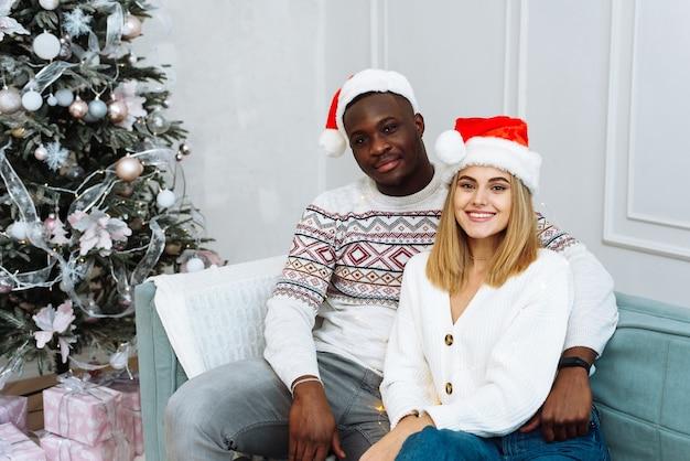 Ein mann und eine frau schauen in die kamera, lächeln in weihnachtsmützen und sitzen auf einem sofa in einem hellen innenraum neben einem weihnachtsbaum.