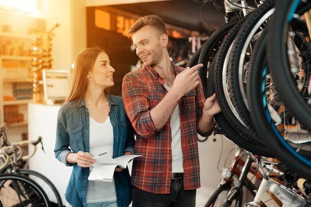 Ein mann und eine frau schauen sich aufmerksam verschiedene fahrräder an