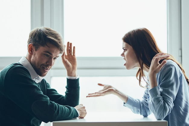 Ein mann und eine frau sitzen an einem tisch und unterhalten sich, streiten sich, ein echter streit, haushaltsprobleme