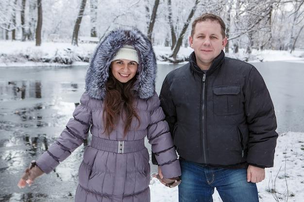 Ein mann und eine frau stehen nahen fluss im schneebedeckten park am wintertag