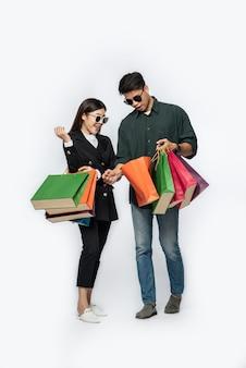 Ein mann und eine frau trugen eine brille und trugen viele papiertüten zum einkaufen