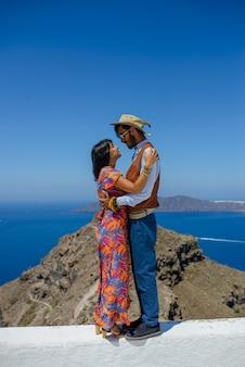 Ein mann und eine frau umarmen sich auf der insel santorin gegen den skaros-felsen. das dorf imerovigli. er ist ein ethnischer zigeuner. sie ist eine israeliin.