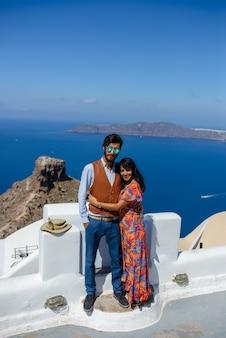 Ein mann und eine frau umarmen sich gegen das meer. das dorf imerovigli. er ist ein ethnischer zigeuner. sie ist eine israeliin.