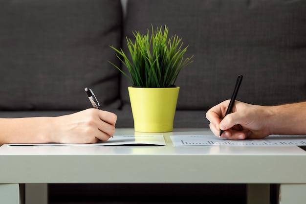 Ein mann und eine frau unterzeichnen eine scheidungsvereinbarung, nahaufnahme. familienstreit, showdown, aufteilung des eigentums, scheidungsvertrag