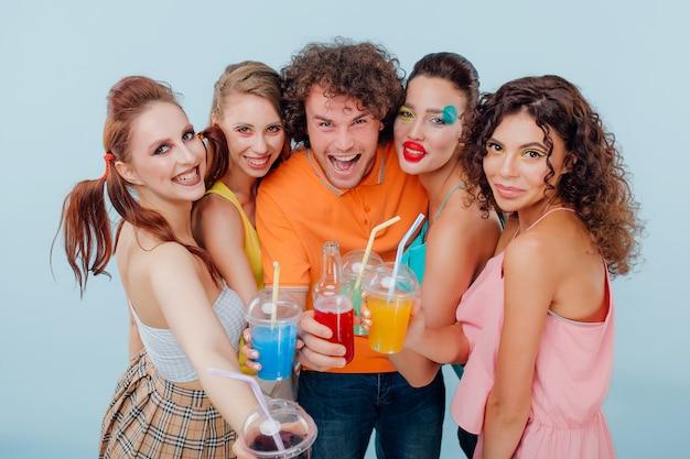 Ein mann und vier mädchen mit buntem make-up halten plastikbecher und lächeln