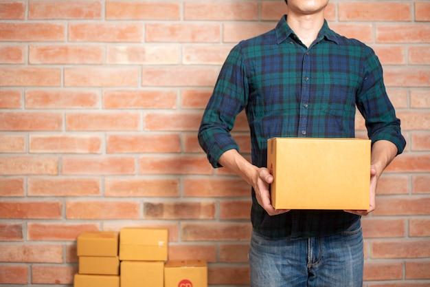 Ein mann unternehmer inhaber kmu-geschäft ist verpackung box, um seinen kunden zu senden