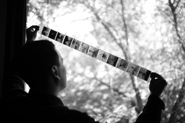 Ein mann untersucht einen mittelformatfilm gegen ein fenster. vintage alt. horizontal