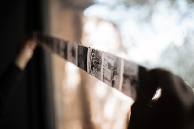 Ein mann untersucht einen mittelformatfilm gegen ein fenster. vintage alt