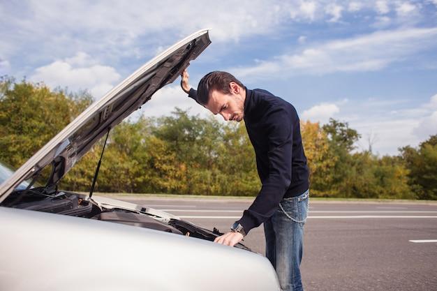Ein mann versucht, das auto auf der straße zu reparieren