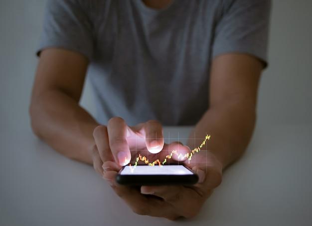 Ein mann verwendet das überprüfen eines geschäftsgraphen mit einer hand-touchscreen-smartphone-technologie