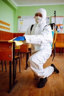 Ein mann von der desinfektionsgruppe räumt mit einem gelben lappen den schreibtisch in der schule auf. professioneller arbeiter sterilisiert das klassenzimmer, um die ausbreitung von covid-19 zu verhindern. gesundheitswesen von schülern und studenten konzept.