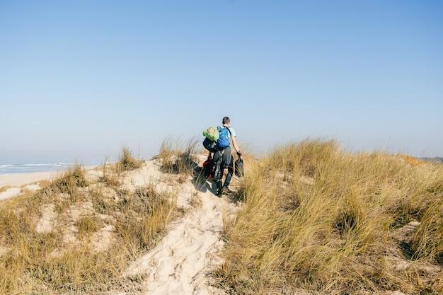 Ein mann von hinten geht mit vielen taschen durch sanddünen