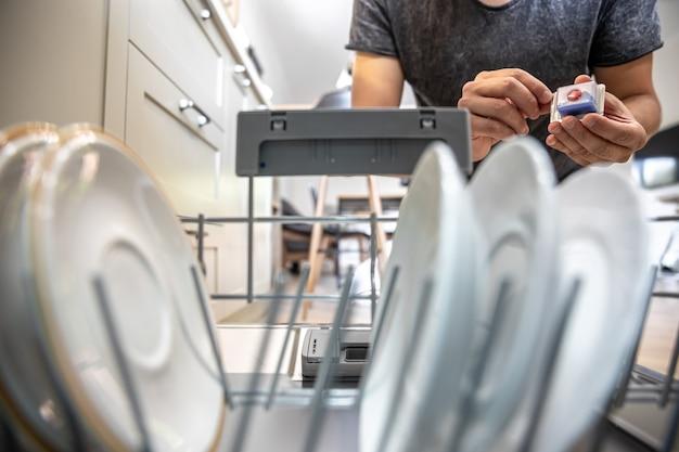 Ein mann vor einer offenen spülmaschine hält eine tablette spülmittel in die spülmaschine.