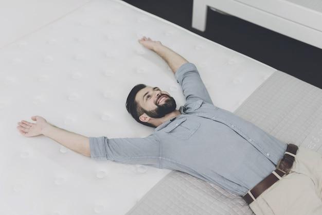 Ein mann wählt sich im laden eine matratze aus