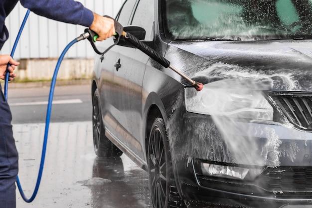 Ein mann wäscht ein auto an der selbstbedienungsautowäsche. hochdruckreiniger sprüht schaum