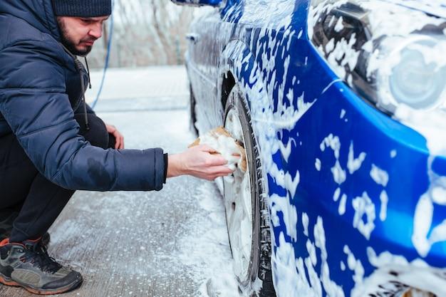 Ein mann wäscht titanscheiben mit einem waschlappen. selbstbedienungs-autowaschanlage