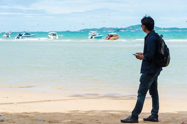 Ein mann wartete auf eine bootsfahrt am strand.