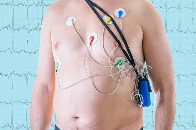Ein mann wird einer herzuntersuchung auf dem hintergrund eines kardiogramms unterzogen.