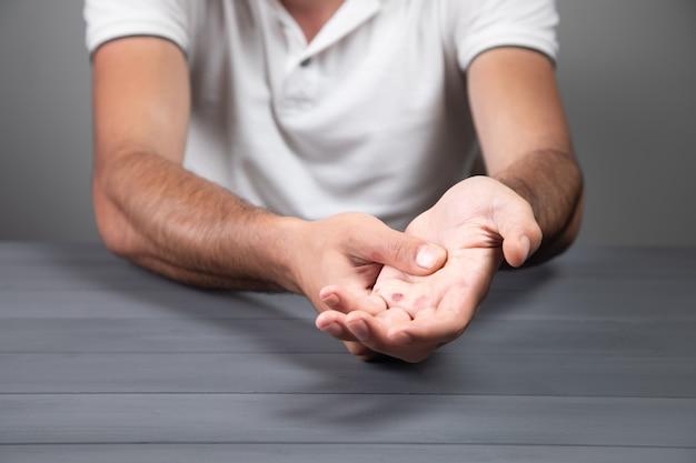 Ein mann zeigt einen kallus an einer grauen wand