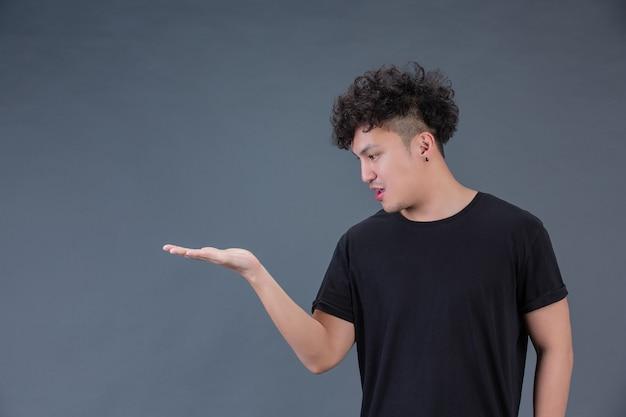 Ein mann zeigt seine hände auf einer pose