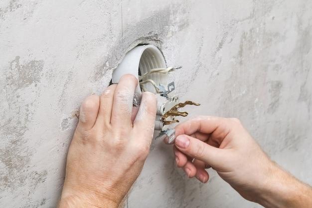 Ein mann zerlegt und repariert eine steckdose für reparaturen. steckdose.