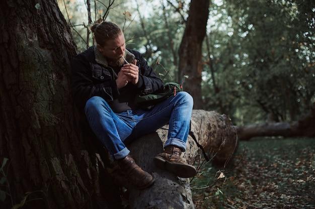 Ein mann zündet sich eine zigarette an, die auf dem stamm eines umgestürzten baumes im wald sitzt. herbstwald