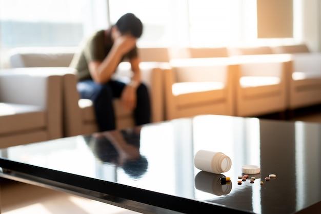 Ein manndruck, der auf stuhl im krankenhaus mit medizin sitzt
