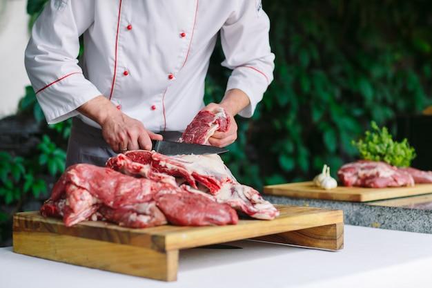 Ein mannkoch schneidet fleisch mit einem messer in einem restaurant.