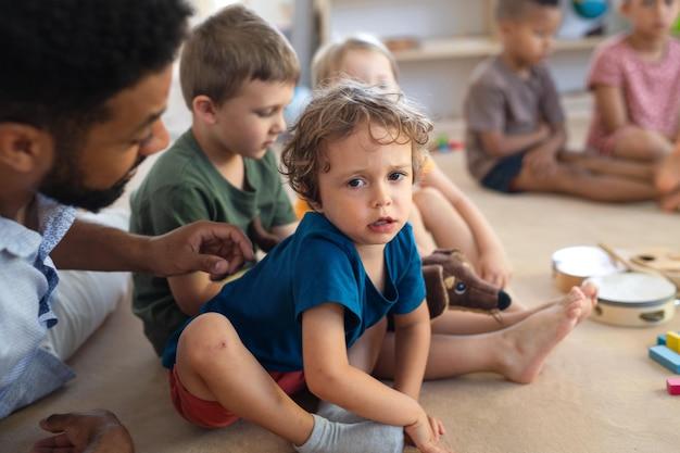 Ein mannlehrer, der drinnen im klassenzimmer mit einem kleinen unglücklichen jungen spricht und ihn tröstet.