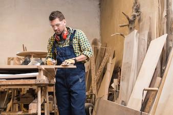 Ein männlicher Tischler, der in der Werkstatt arbeitet