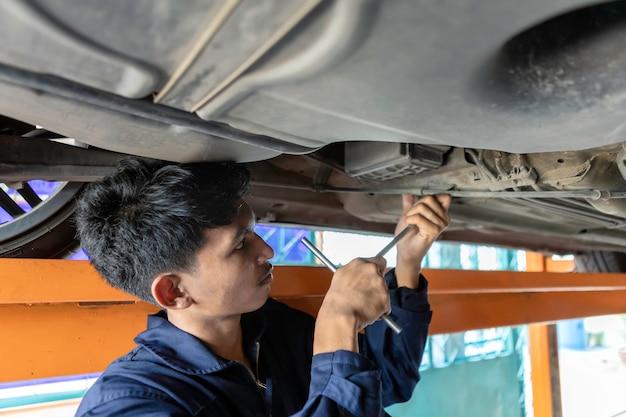 Ein mannmechaniker repariert den motor auf der hebebühne. durch die verwendung von autoreparaturwerkzeugen in der garage. service-auto-konzept.