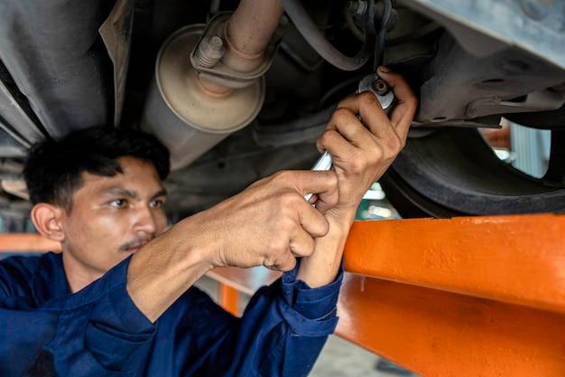 Ein mannmechaniker repariert den motor auf der hebebühne. durch die verwendung von autoreparaturwerkzeugen in der garage.