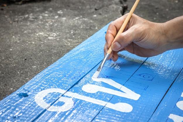 Ein mannschreiben unterzeichnet brett mit einer bürste von aquarellen auf zementbodenhintergrund